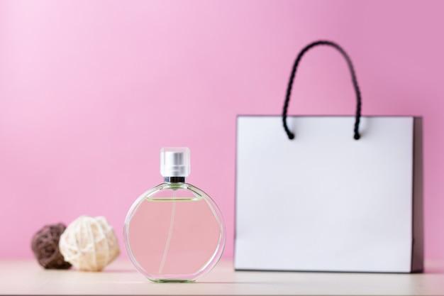 Butelka ulubionych perfum damskich i papierowa torebka prezent na różowym tle