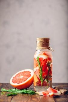 Butelka warzonej wody z plastrami grejpfruta i świeżymi źródłami rozmarynu. składniki i nóż na drewnianym stole