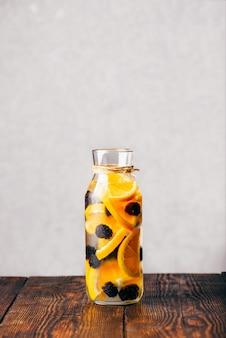 Butelka warzonej wody z plastrami surowej pomarańczy i świeżą jeżyną.