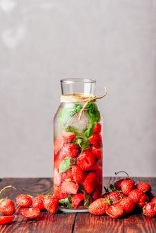 Butelka warzonej wody ze świeżymi liśćmi truskawek i bazylii