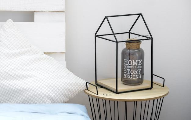 Butelka wazon z cytatem o domu wewnątrz metalowej ramie kształt domu na stole