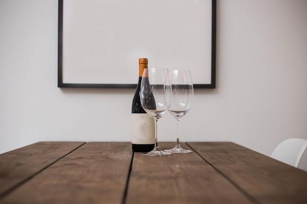 Butelka wina i dwie szklanki na drewnianym stole