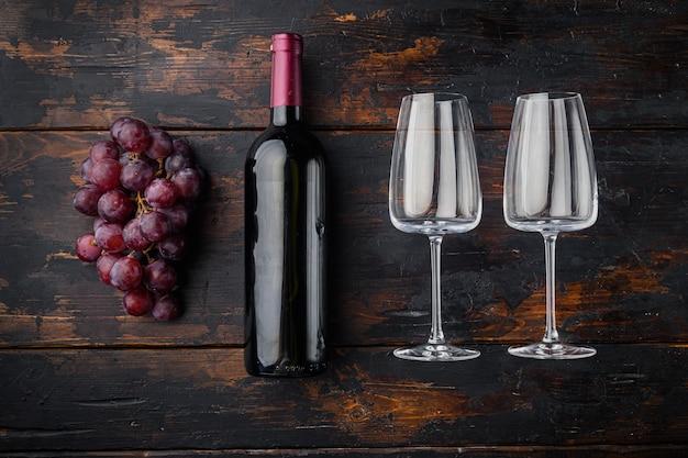 Butelka wina i kieliszek czerwonego wina z dojrzałymi winogronami, na starym ciemnym drewnianym stole, widok z góry płaski leżał