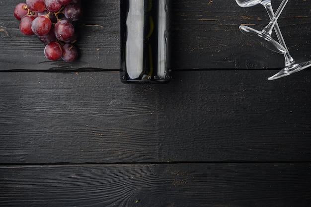 Butelka wina i kieliszek czerwonego wina z zestawem dojrzałych winogron, na tle czarnego drewnianego stołu, płaski widok z góry, z kopią miejsca na tekst
