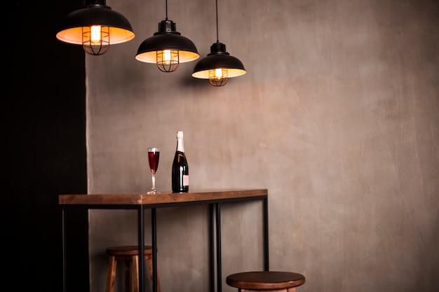 Butelka wina i kieliszek stoją na drewnianym stole w sali restauracyjnej