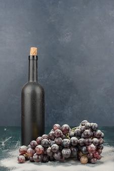 Butelka wina i kiść czarnych winogron na marmurowym stole.