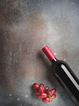 Butelka wina i winogron na ciemnym tle kamienia, kopia przestrzeń, widok z góry