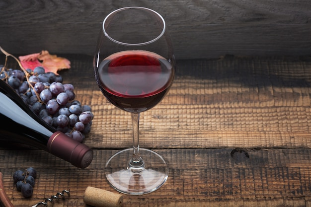 Butelka wina, kieliszek, kiść winogron i liście winogron na starym drewnianym stole.