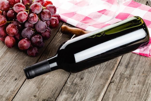 Butelka wina korkociąg i winogrona na drewnianym stole