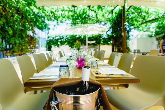 Butelka wina otworzyła się w wiadrze, aby ją schłodzić, w śródziemnomorskiej restauracji z winnicami.