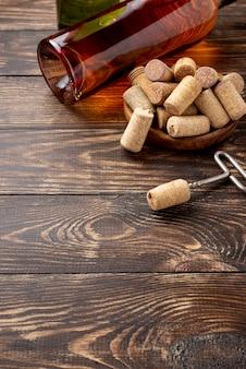 Butelka wina pod wysokim kątem i korki obok