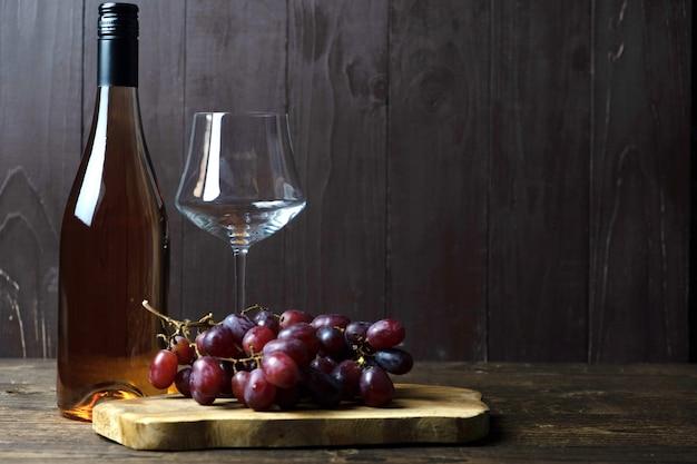 Butelka wina różanego stoi na drewnianym stole, obok pustej szklanki i kiści winogron na drewnianej desce. miejsce na tekst