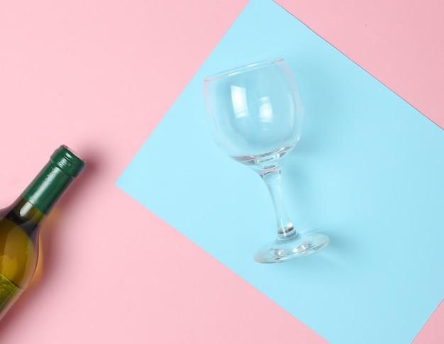 Butelka wina, szkło na kolorowej pastelowej powierzchni. widok z góry. minimalizm