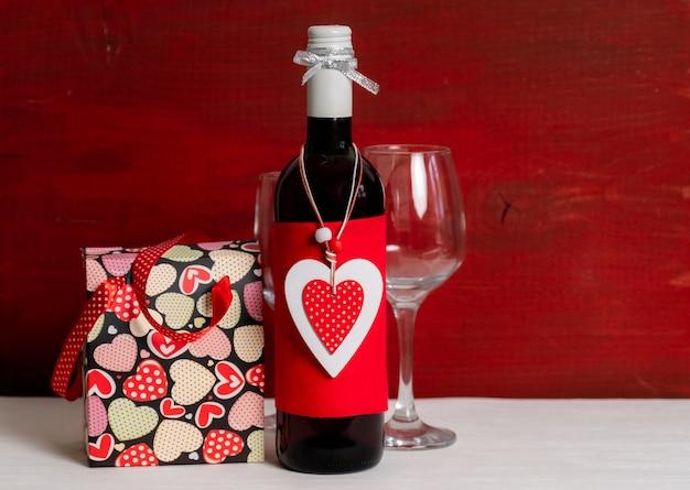Butelka wina, torba na zakupy, białe pudełko i czerwone serce walentynek na czarno