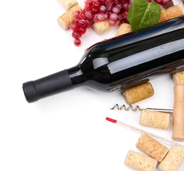 Butelka wina, winogron i korków, na białym tle