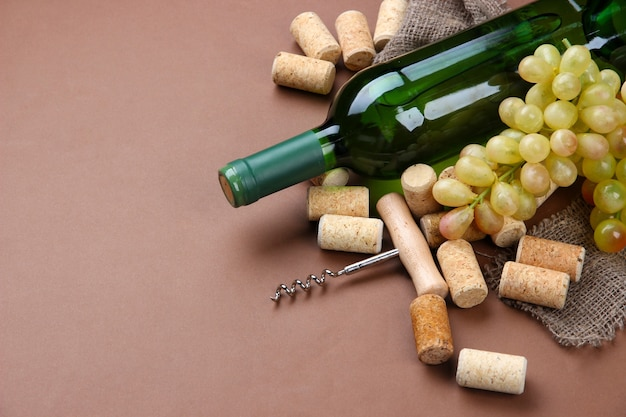 Butelka wina, winogron i korków na brązowym