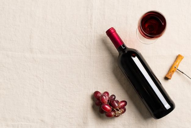 Butelka wina, winogron i szklanki na białym tle włókienniczych, kopia przestrzeń, widok z góry