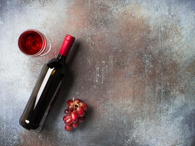 Butelka wina, winogron i szklanki na ciemnym tle kamienia, kopia przestrzeń, widok z góry