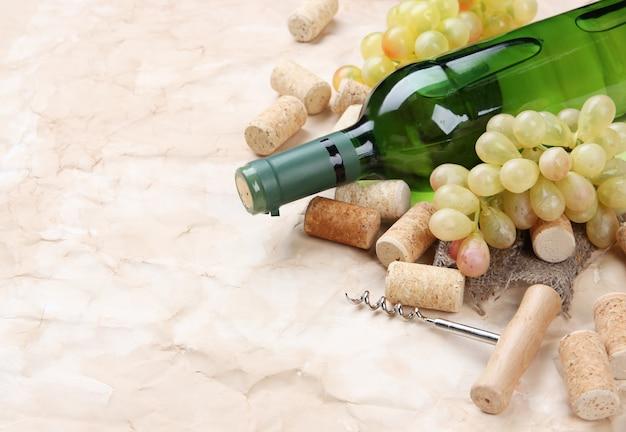 Butelka wina, winogrona i korki na starym papierze