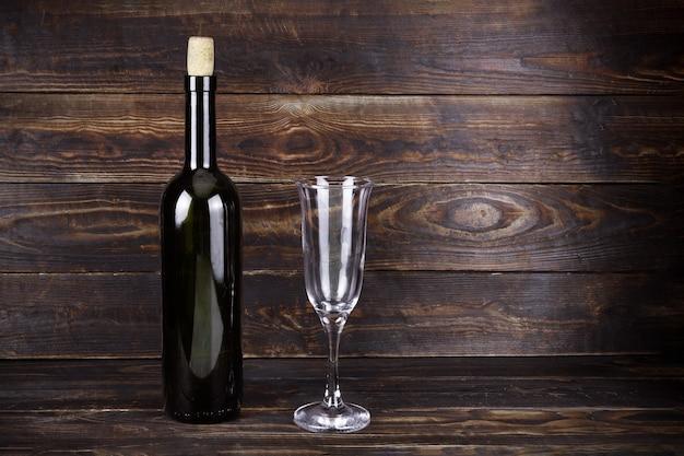 Butelka wina z ciemnego szkła bez etykiety i pusty przezroczysty kieliszek na brązowym tle drewnianej deski.