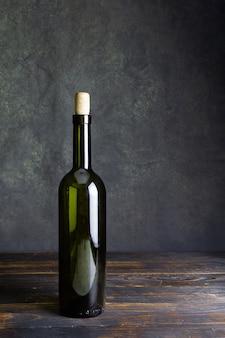 Butelka wina z ciemnego szkła bez etykiety na ciemnym tle na brązowym drewnianym stole.