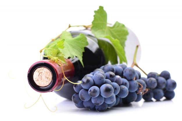 Butelka wina z winogronami na białym tle