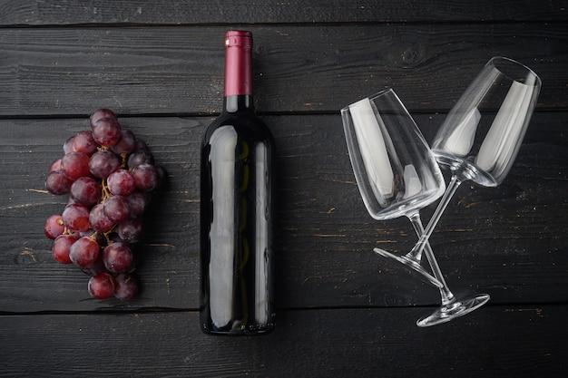 Butelka wina z zestawem winogron na czarnym drewnianym stole, płaski widok z góry