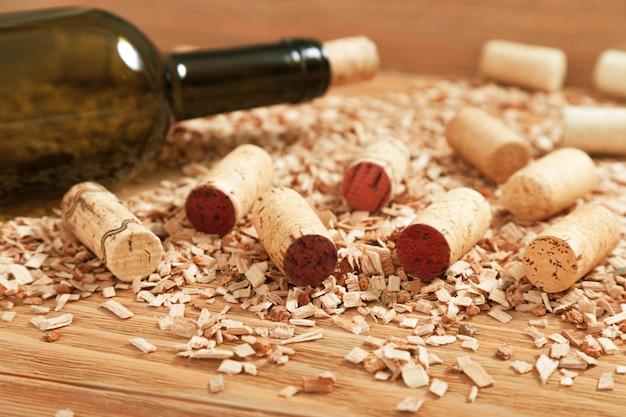 Butelka wina zamknięta korkiem na tle porozrzucanych drewnianych frytek i różnych korków do wina. selektywne ustawianie ostrości.