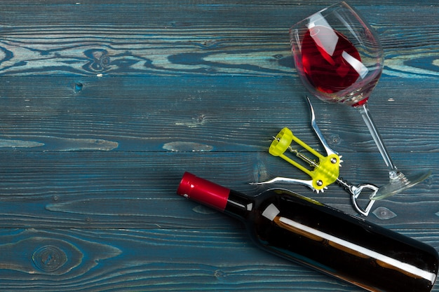 Butelka wino, korek i korkociąg na drewnianym stołowym tle