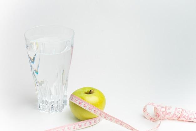Butelka woda, jabłko i pomiarowa taśma odizolowywająca na białym tle