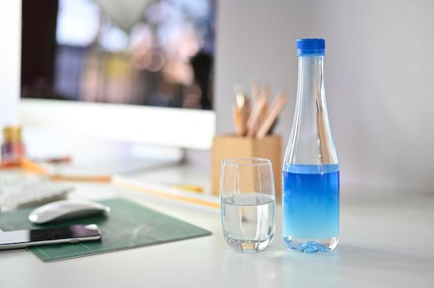 Butelka wody i szklankę wody na biurku.