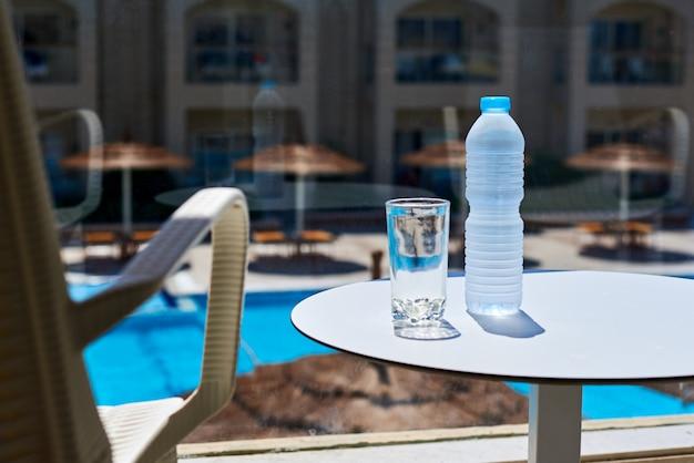 Butelka wody i szklanki na stole na tarasie w hotelu przed basenem z wodą
