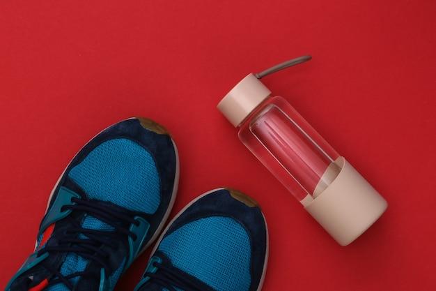 Butelka wody i trampki na czerwonym tle. zdrowy styl życia, trening fitness. widok z góry