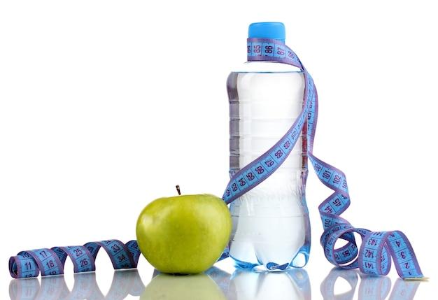 Butelka wody, jabłka i miarkę na białym tle