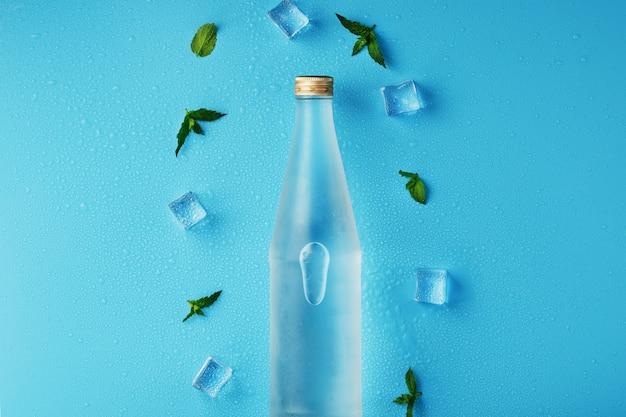 Butelka wody lodowej, kostki lodu, krople i listki mięty