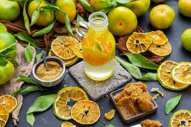 Butelka wody mandarynkowej na stole w otoczeniu suchych cytrusów, proszku mandarynki i dżemu