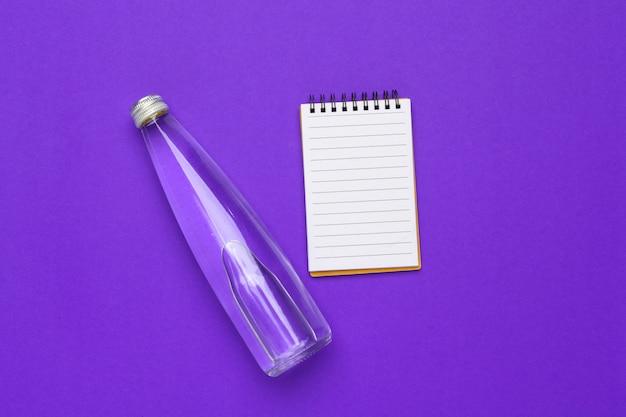 Butelka wody płaskie leżał widok z góry na fioletowy papier
