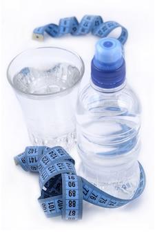 Butelka wody, szklanka wody i taśma miernicza na białym tle