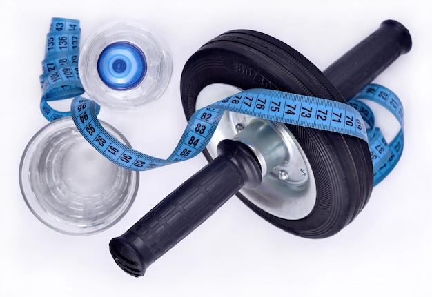 Butelka wody, szklanka wody, rolka na mięśnie brzucha i taśma miernicza widok z góry
