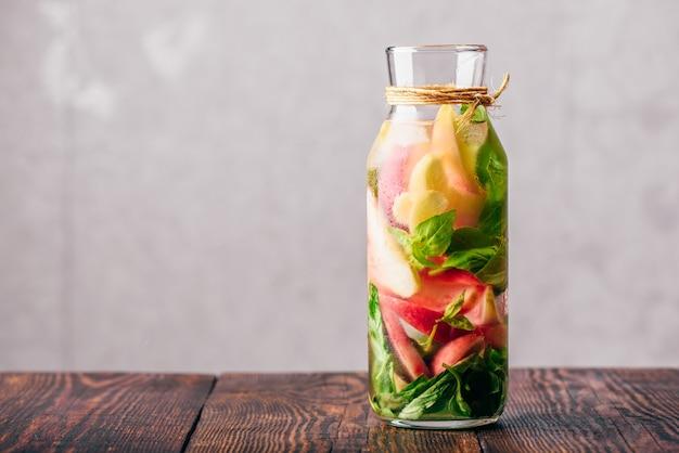 Butelka wody z plastrami brzoskwini i liści bazylii.