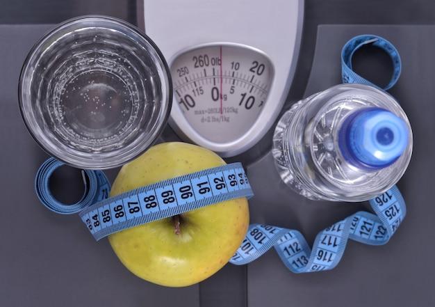 Butelka wody, zielone jabłko, szklanka wody i miarka na wadze
