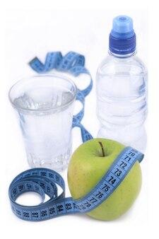 Butelka wody, zielone jabłko, szklanka wody i taśma miernicza na białym tle