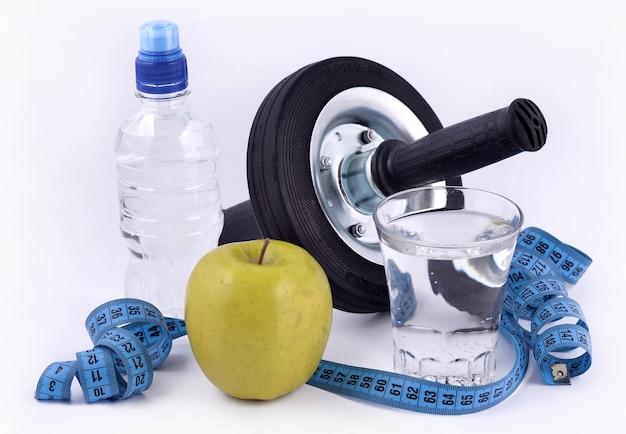 Butelka wody, zielone jabłko, szklanka wody, rolka do brzucha i miarka na białym tle