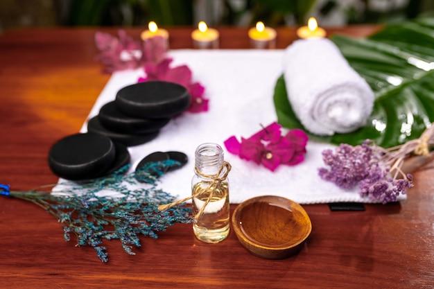 Butelka z aromatycznym olejem, kubek z wlanym olejem umieszczony przed ręcznikiem frotte, na którym znajdują się kamienie do kamienia terapeutycznego, zwinięty ręcznik, różowe kwiaty i suszone gałązki lawendy