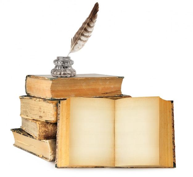 Butelka z atramentem i pióro na stos starych książek i jedna otwarta książka z pustymi stronami na białym tle