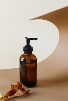 Butelka z brązowego szkła na kosmetyki z suchym liściem na brązowym tle