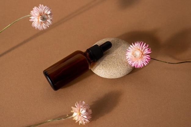 Butelka z brązowego szkła z olejkiem kosmetycznym z różowymi suchymi kwiatami na tle terakoty widok z przodu, zbliżenie