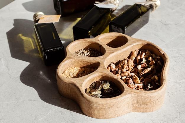 Butelka z ciemnego szkła wielokrotnego użytku i różne nasiona orzechów. ekologiczne opakowanie jest wielokrotnego użytku. zero marnowania.