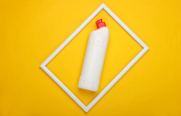 Butelka z detergentem na żółtej powierzchni z białą ramką