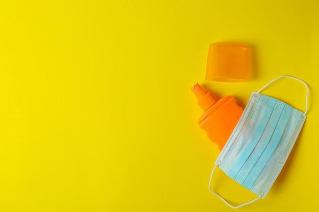 Butelka z filtrem przeciwsłonecznym i maską medyczną na żółto
